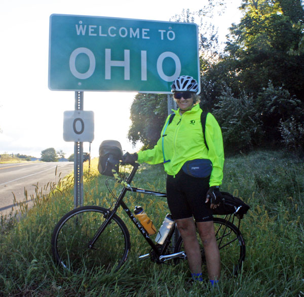 "Kathy poses by the ""Welcome to Ohio"" sign."